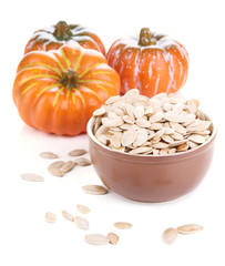 Pumpkin seeds in bowl with pumpkins isolated on white
