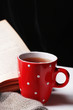 Cup of hot tea with book and plaid on table on dark background