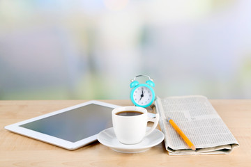 Tablet, newspaper, cup of coffee and alarm clock on wooden
