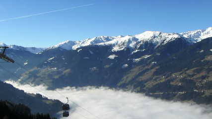 Gondola lift above the fog in valley, Alps, Austria, time lapse
