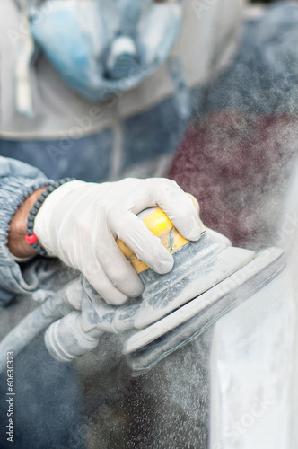 Young auto mechanic using the power buffer machine for painting