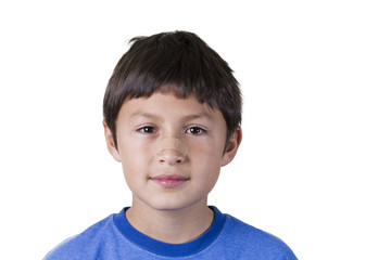 Young boy with plaster on his nose - on white background