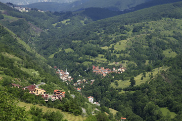 Village with red roofed houses in the wooded mountains in Kosovo