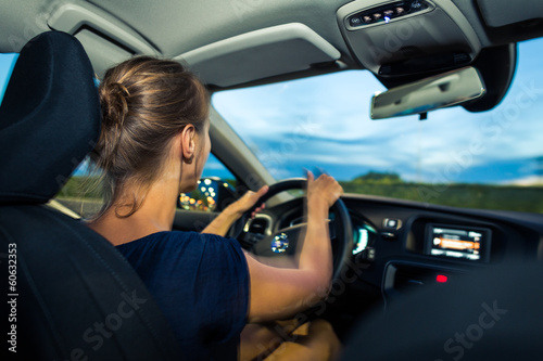 Young, woman driving a car at dusk, going home from work