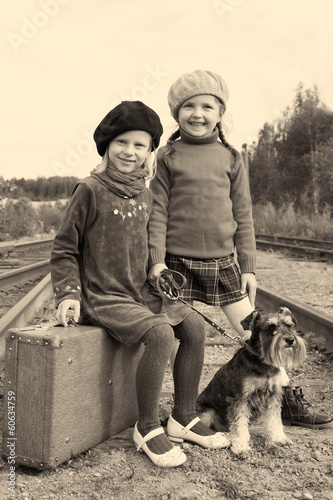 Two girls and a dog go by rail