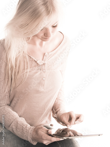 young woman sitting using an Ipad resting on her knee