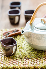 Cup of tea and teapot on wooden