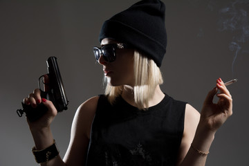 Beautiful girl with a gun in his hand and smoking a cigarette.