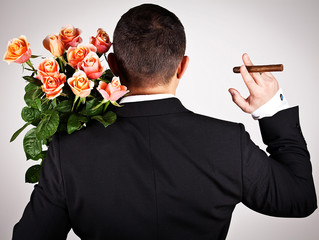 Young man in suit with bouquet of roses