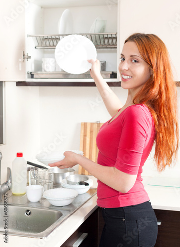 Smiling woman washing dishes in the kitchen