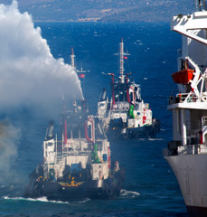 Burning ship and Fire Fighting Boat sprays jets of water