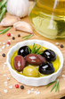 three kinds of olives in a bowl with olive oil and spices
