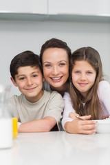 Closeup of a smiling mother with kids in kitchen