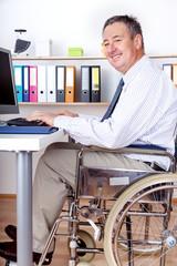 Man in wheelchair at desk