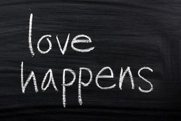 The phrase Love Happens written on a blackboard