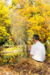 Man sitting in autumn leaves by the lake