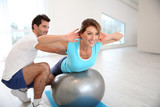 Woman doing pilates exercises with coach - 60644785