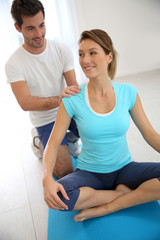Woman with sports trainer in gym