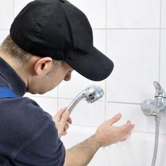 Sanitär-Installateur repariert Dusch-Kopf im Bad