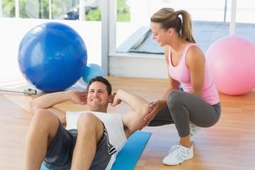 Female trainer looking at young man do abdominal crunches