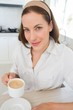 Smiling young woman with coffee cup in kitchen