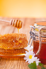 Honey with honeycomb and wooden drizzler