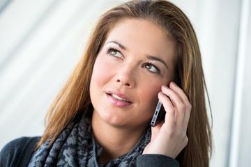 junge Frau mit Smartphone nachdenklich