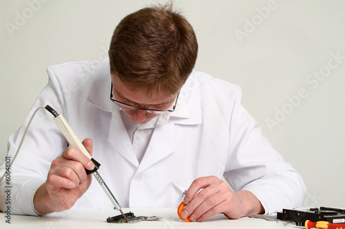 soldering iron in his hand