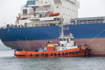 red tug boat assisting huge ship in port