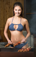 girl cooks meat on a barbecue grill