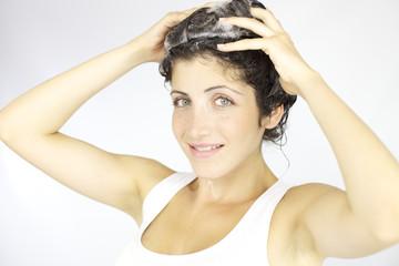 Happy woman washing hair with shampoo