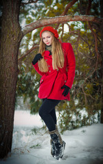 Attractive blonde girl with gloves, red coat and red hat posing