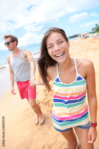 Beach people - young couple holding hands walking