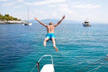 Freiheit, Abenteuer - Mann springt vom Boot aus ins Meer