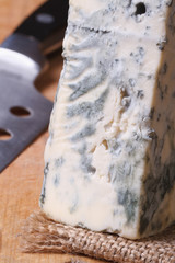 Blue cheese on a kitchen board and knife. vertical macro.