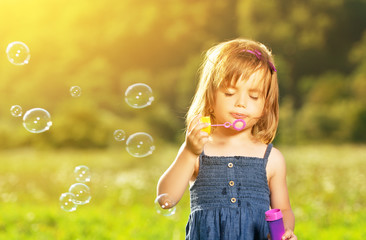little girl blowing soap bubbles in nature