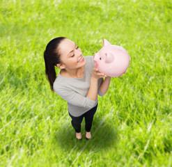 happy woman looking at piggy bank