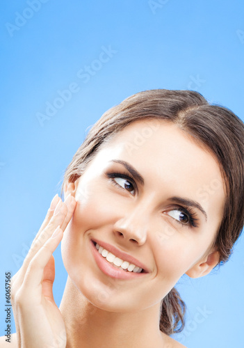 Woman touching skin or applying cream, over blue
