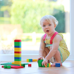 Adorable toddler girl playing with plastic blocks