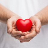 mans cupped hands showing red heart