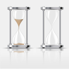 Sand falling in the hourglass on dark background