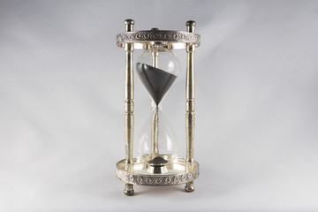 Hourglass – old fashioned hourglass, black sand, half full.