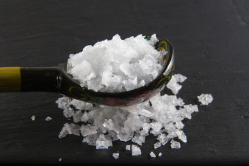 Sea salt flakes, on a wooden spoon and scattered. Macro.