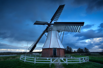 Dutch windmill over storm sky