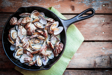 Cast iron skillet of Delicious Fresh Steamer Clams with Garlic a