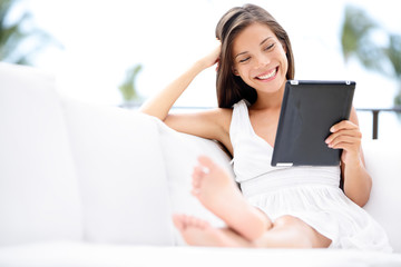 Young woman with tablet computer smiling, reading