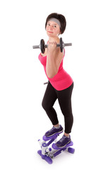 The girl is engaged in fitness with dumbbells on stepper.