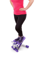 The girl is engaged in fitness stepper. On a white background.