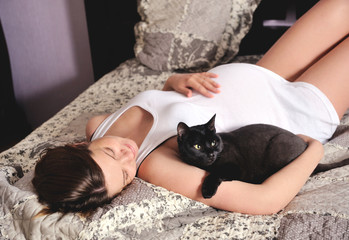 Smiling pregnant woman with cat at home.