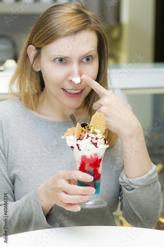 Young woman tasting cup of ice cream